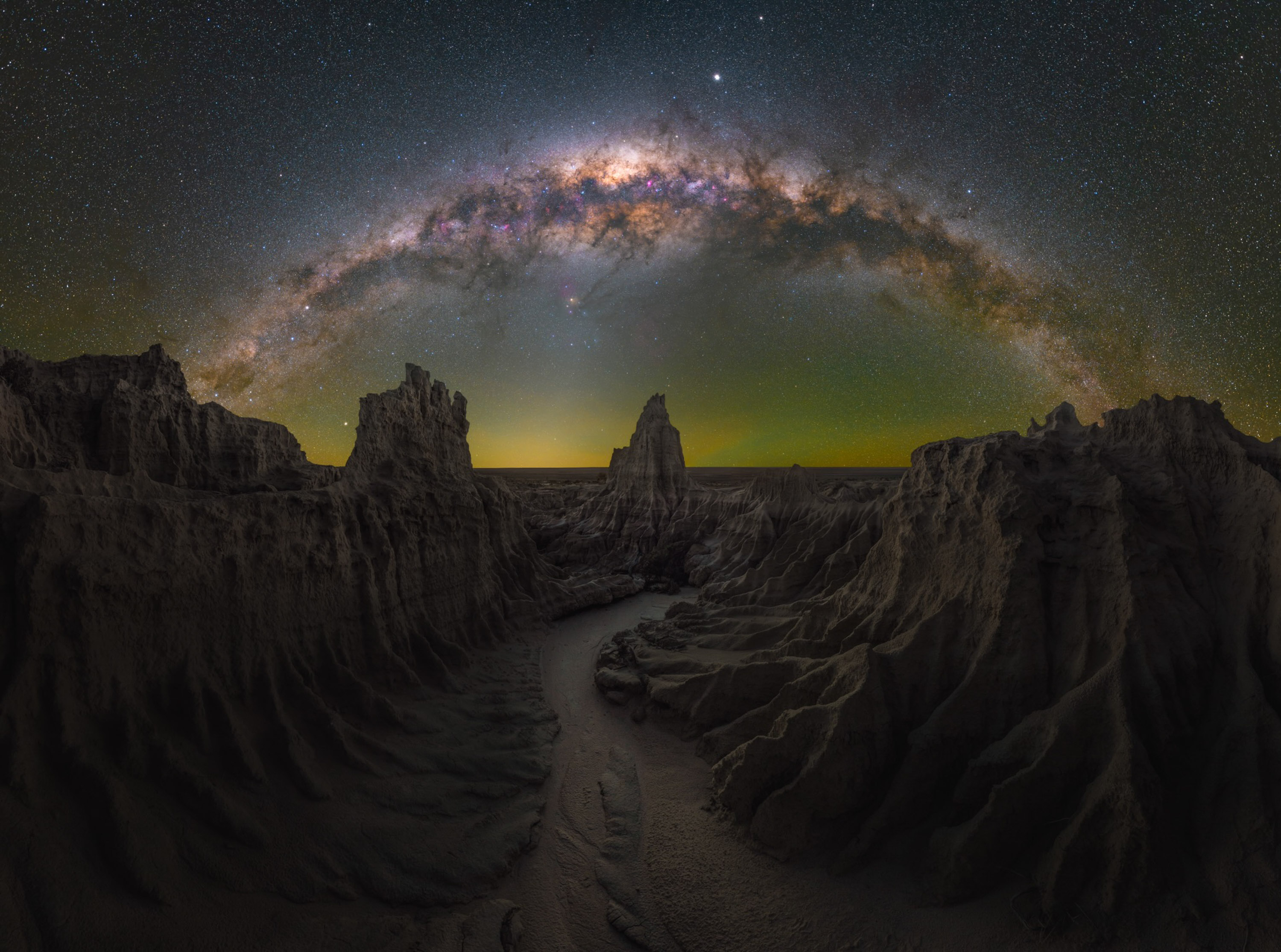 Dragon's Lair, shot in Mungo, New South Wales, Australia. The Milky way arcs over a canyon where jagged cliffs frame a winding path, leading to a central spire. A faint golden glow emanates from the horizon.