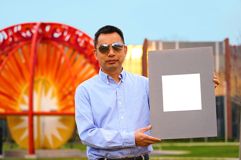 Study author Xiulin Ruan with his lab's sample of the whitest paint on record