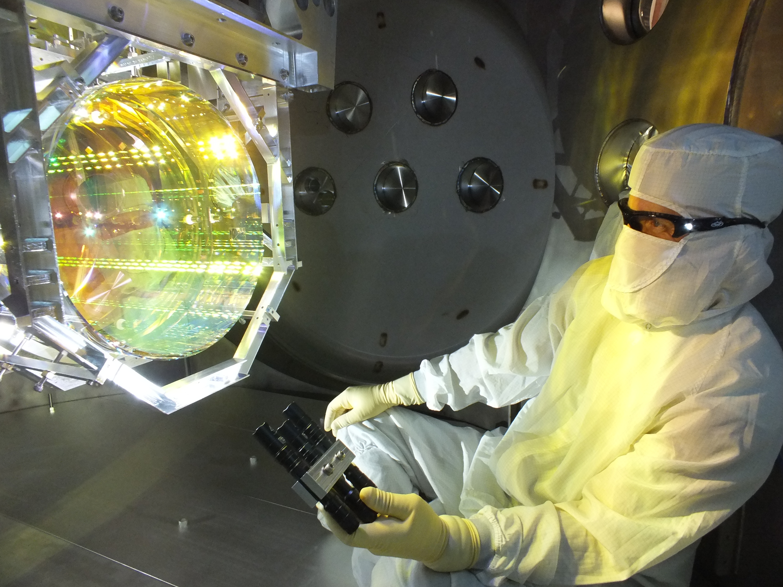 A scientist inspecting one of LIGO's mirrors, which has now been measurably affected by quantum fluctuations