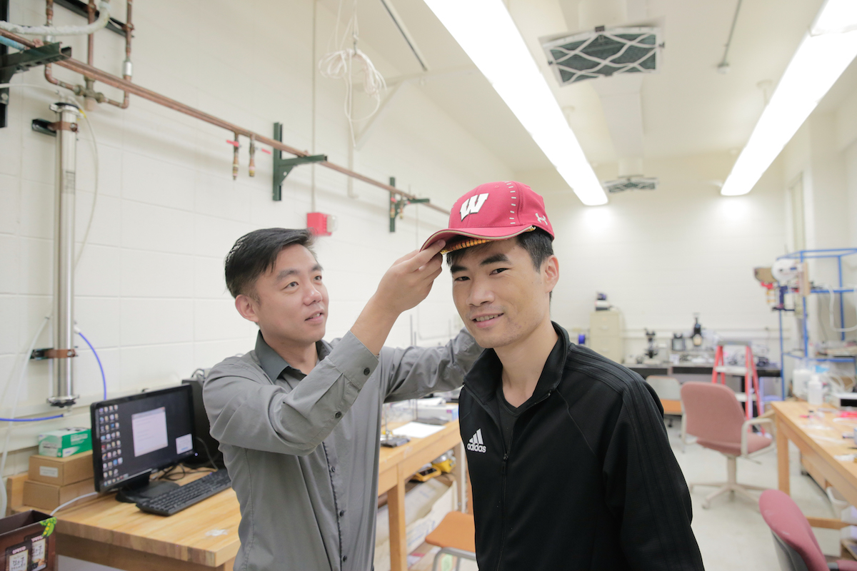 Hair-growth-stimulating device fits under a baseball cap