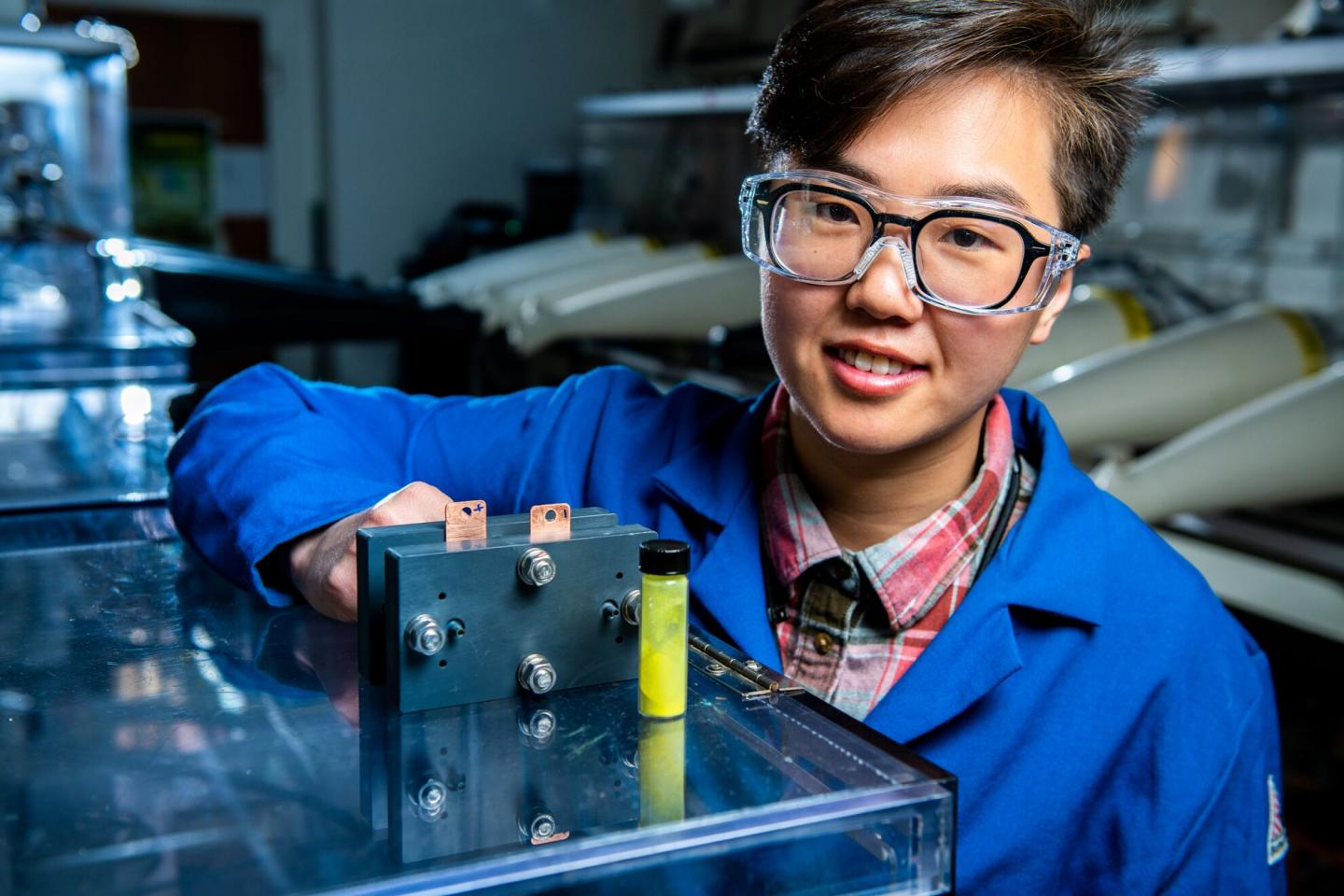 Researcher scientist Ruozhu Feng with a novel redox flow battery developed at PNNL