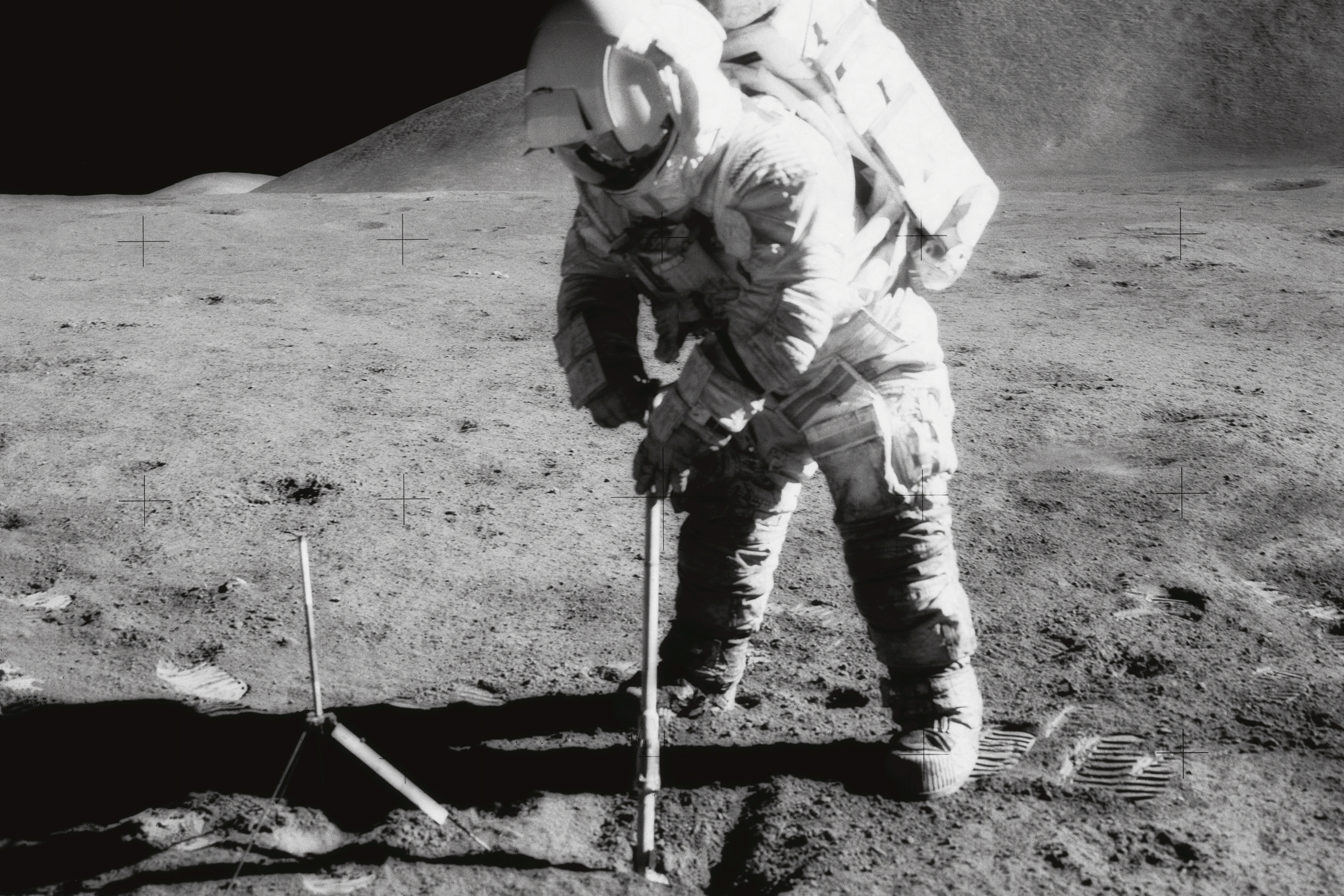 Astronaut James B. Irwin collects soil from the surface of the moon during the Apollo 15 mission