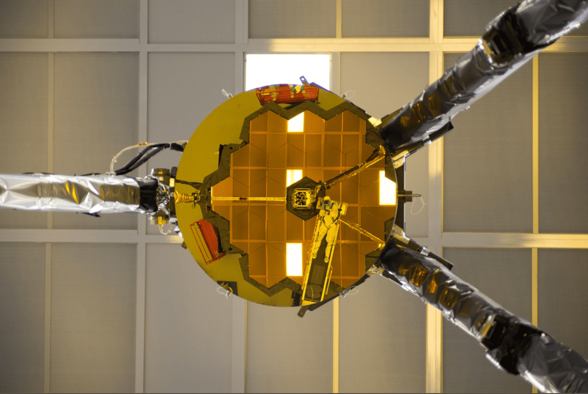 Ball Aerospace optical engineer Larkin Carey is reflected in the James Webb Space Telescope's secondary mirror, as he photographs the line of sight for hardware used during an important test of the telescope's optics