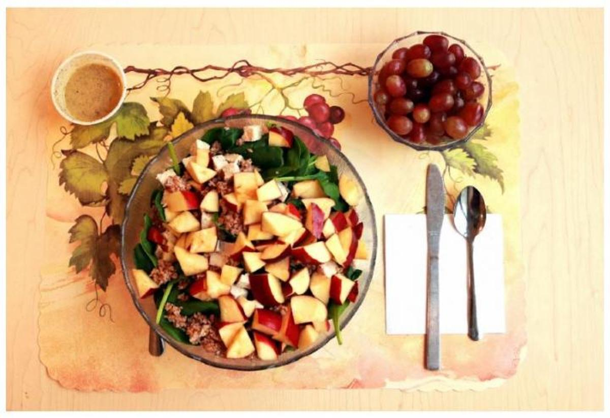 This image shows one of the study's unprocessed lunches, consisting of a spinach salad with chicken breast, apple slices, bulgur, and sunflower seeds and grapes