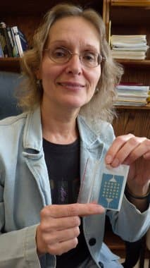 Elena Semouchkina holds the ceramic resonators that enable her to make objects appear invisible in microwave frequencies