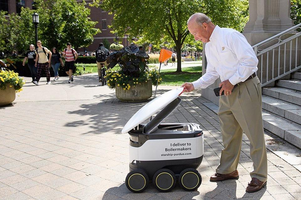 Purdue University president Mitch Daniels receives a robotic food delivery