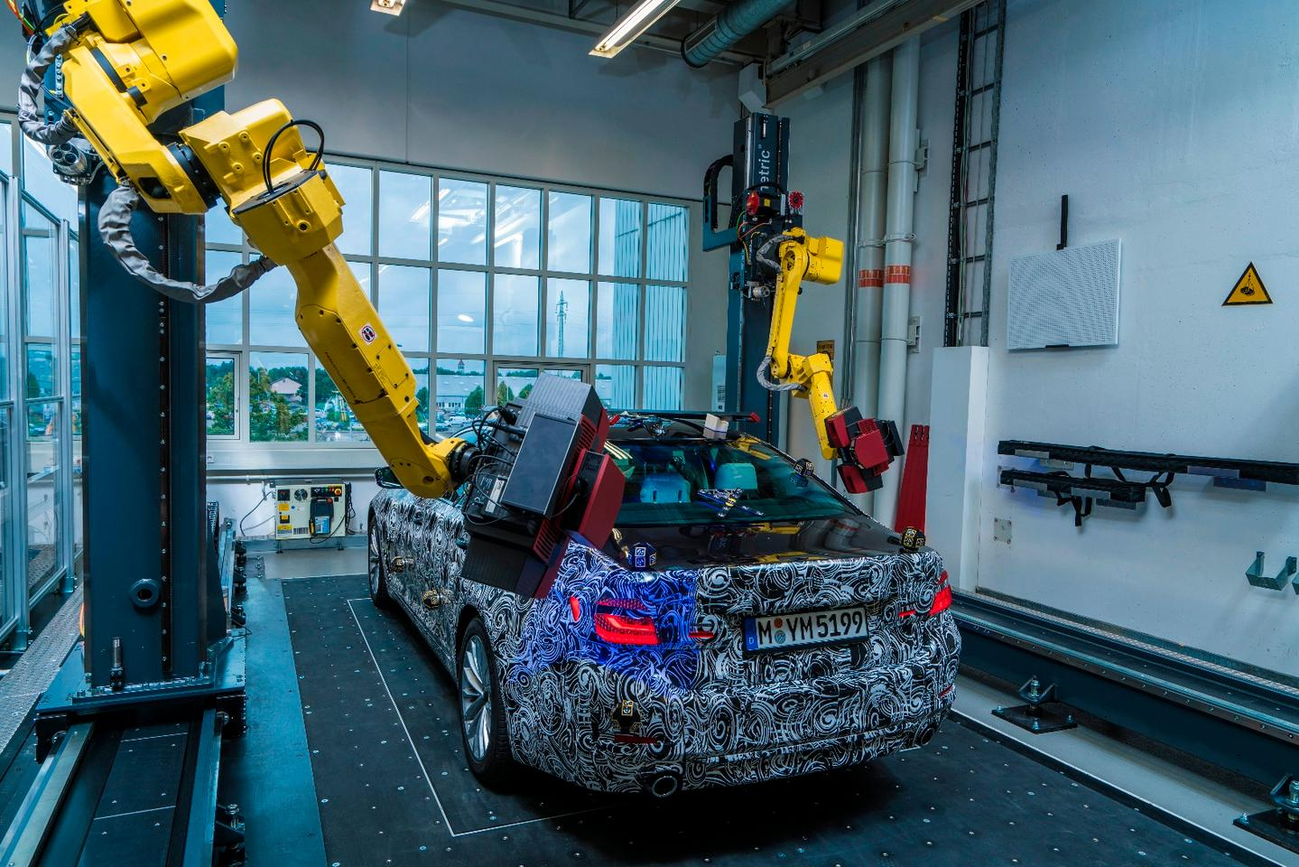 Two robotic arms mounted with sensors scan a vehicle in parallel