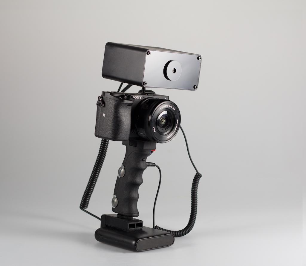 The box mounted to the top of a mirrorless or DSLR camera constantly monitors scenes out front, and triggers the photographer to capture a shot with an electric shock via the grip