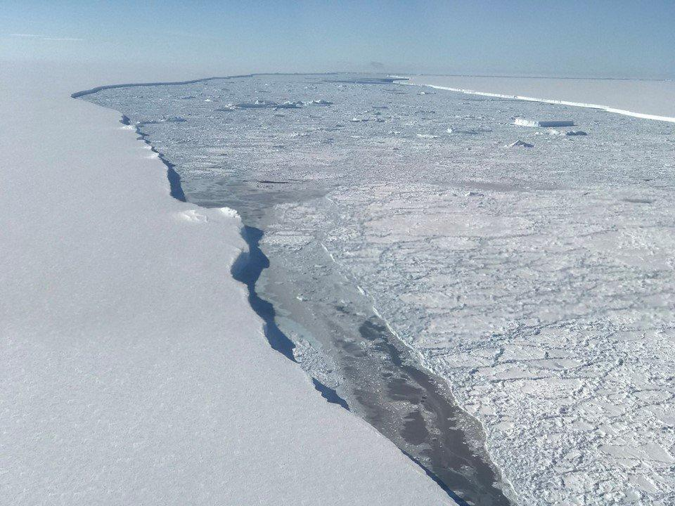 The edge of Larsen C Ice Shelf with the western edge of iceberg A68 in the distance at the top right