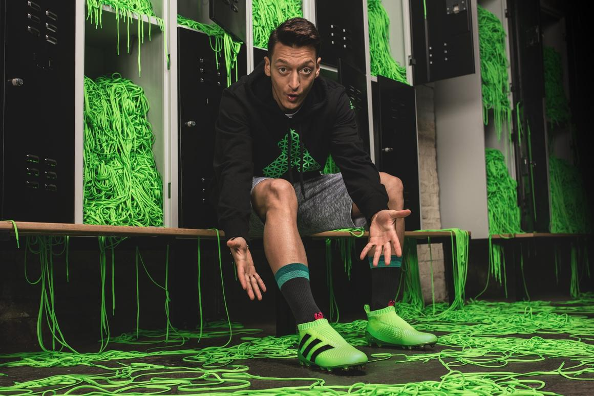 Arsenal's Mesut Ozil tries on a pair of Adidas' laceless football boots