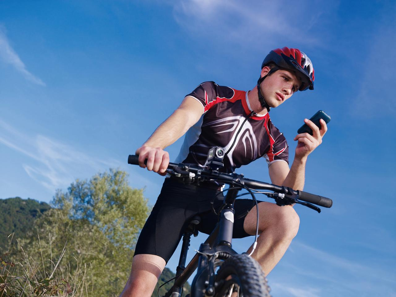 A mountain bike rider checks uses his mobile phone to monitor the video recorded by the action cam