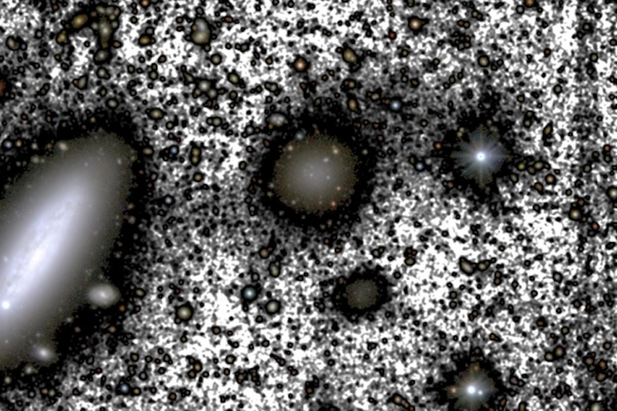 A composite color image of galaxy NGC1052-DF4 (center), which is losing mass to a larger nearby galaxy NGC1035 (left). The grey shading indicates stars that are already bing pulled out of their home galaxy