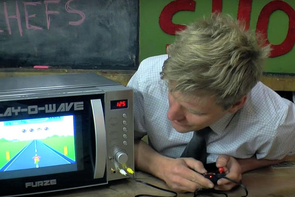Colin Furze plays an old school video game while waiting for his meal to cook