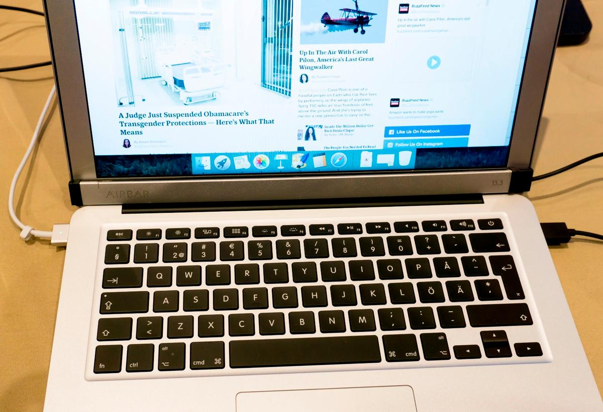 The Touch Bar sits below the MacBook Air's screen