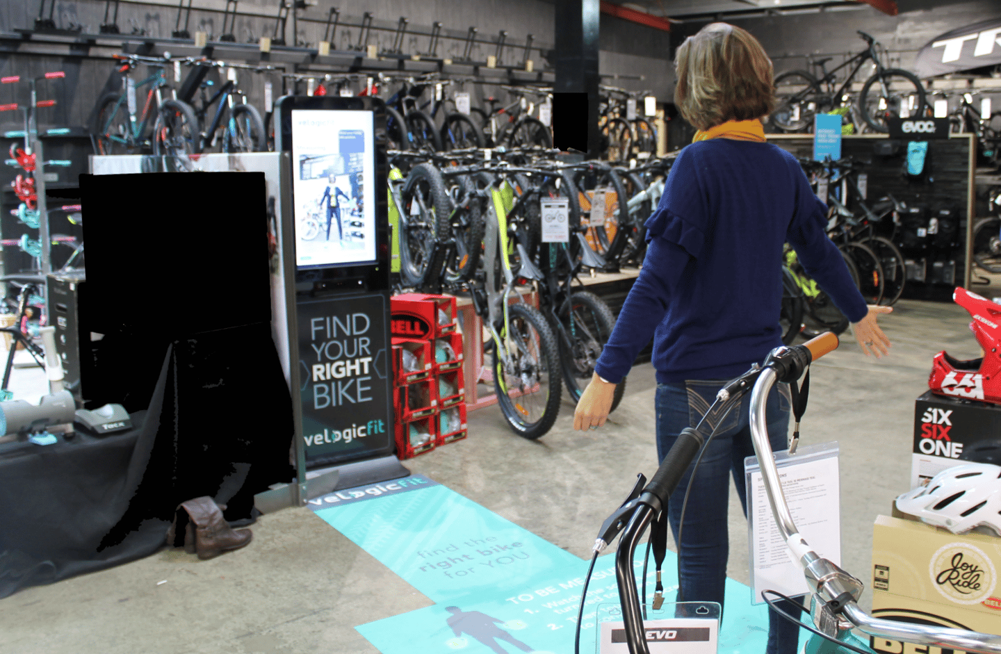 Bike buyers stand in front of the Right Bike kiosk and are measured up before the system helps them choose a bike that fits their needs