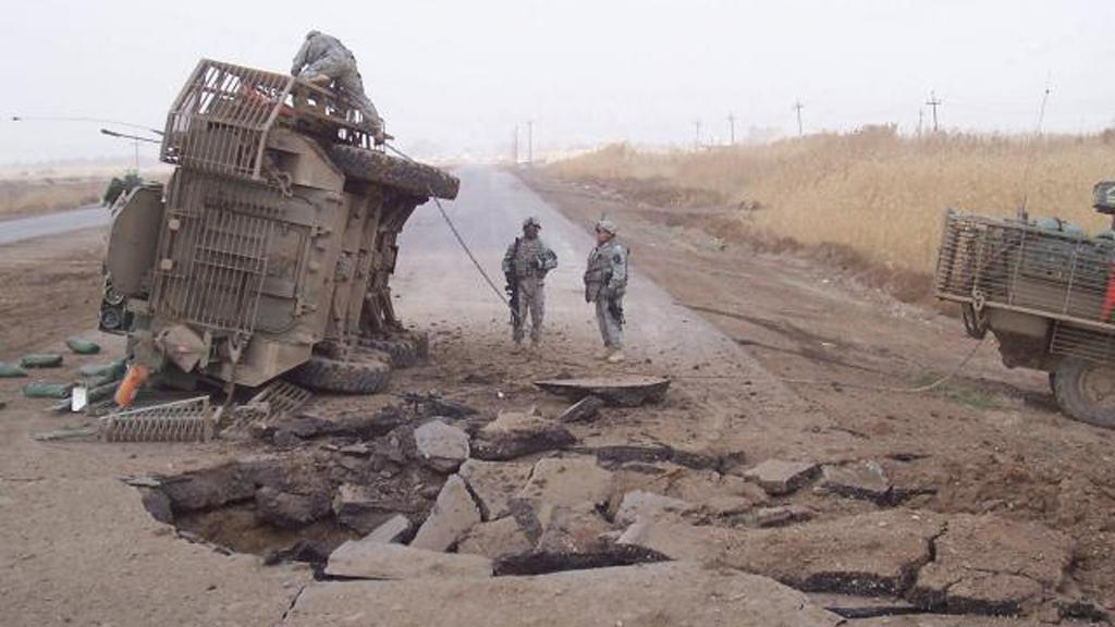 A Stryker lies on its side following a buried IED blast in Iraq in 2007