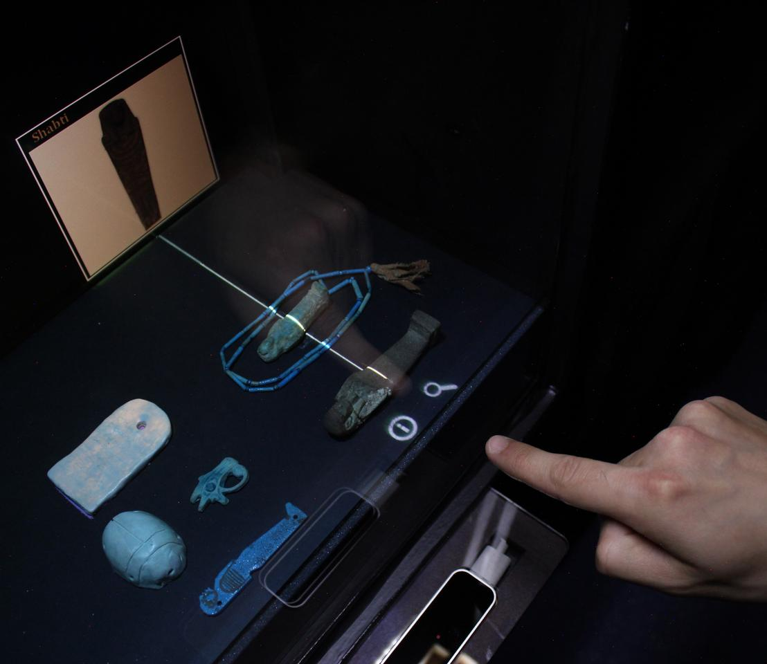 "The reflection of a user's finger ""touches"" a museum artifact, causing a projected pop-up to appear"