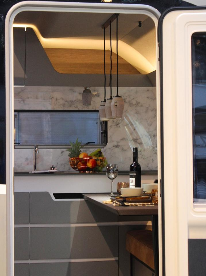 A peek inside the Harmony 3 doorway reveals the hanging dining area lights and stone-look kitchen wall