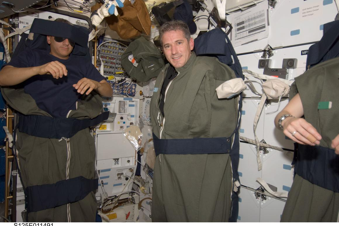 Astronauts Mike Massimino (left) and Michael Good (right) strap in for a night's sleep aboard the Space Shuttle Atlantis (Photo: NASA)
