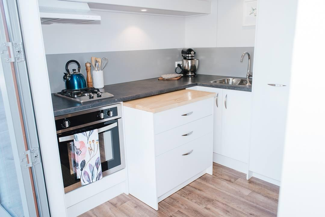 The Larissa and Tyler Tiny House's kitchen includesa pull-out cabinet that reveals a washing machine