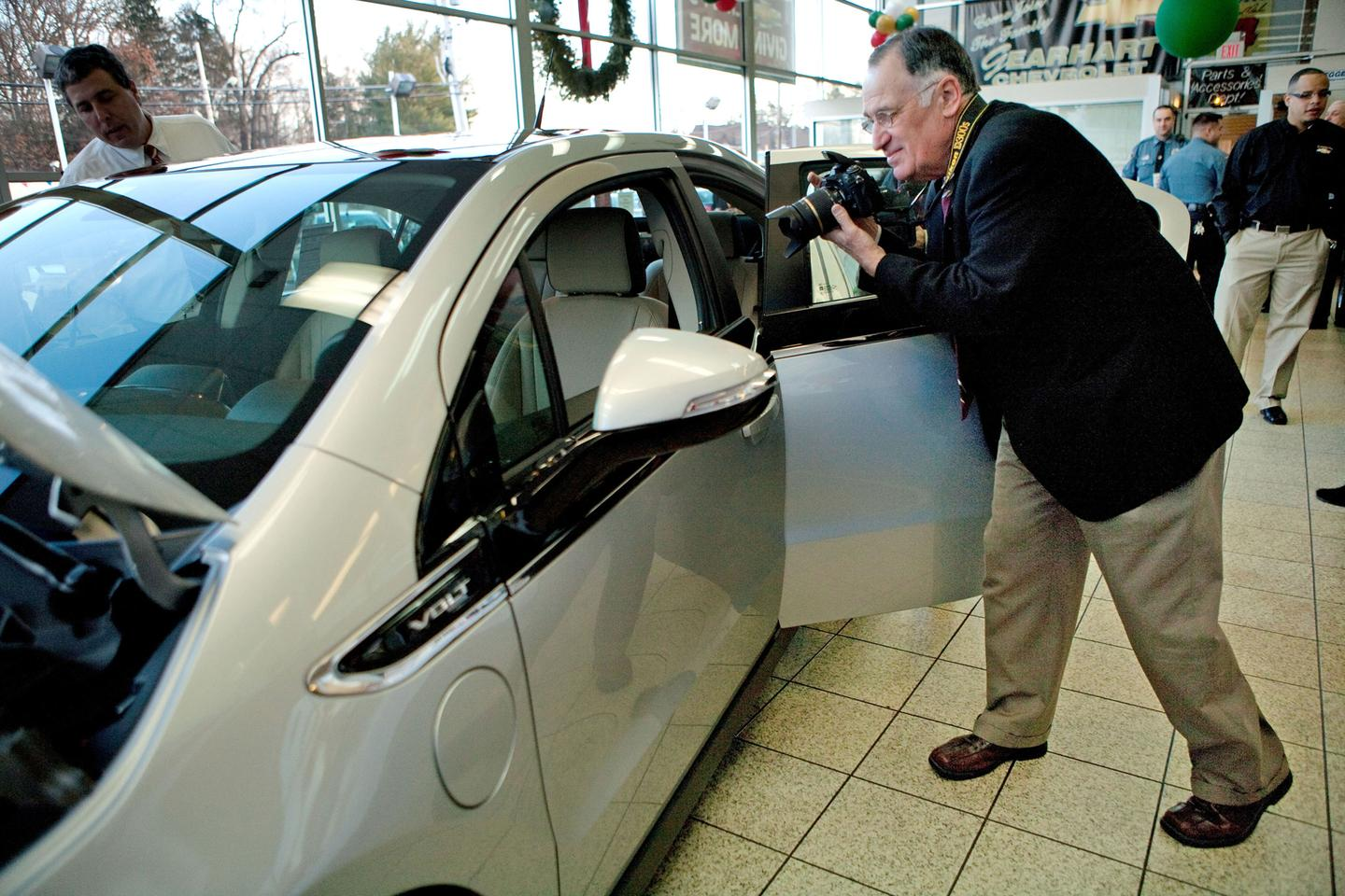 Jeffrey Kaffee takes pictures of his new Chevrolet Volt - presumably for insurance purposes or something (Image: Emile Wamsteker for Chevrolet)