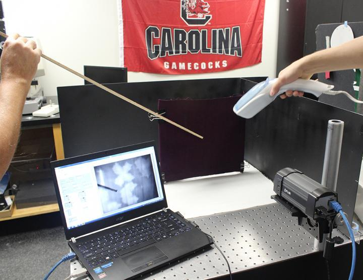 A hand steamer and an infrared camera are used to reveal blood markings on a black background