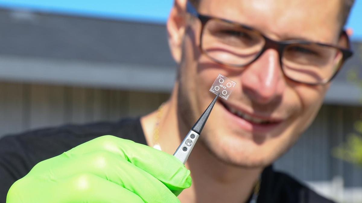 ResearcherMatthieu Rüegg with a sample of the microresonator