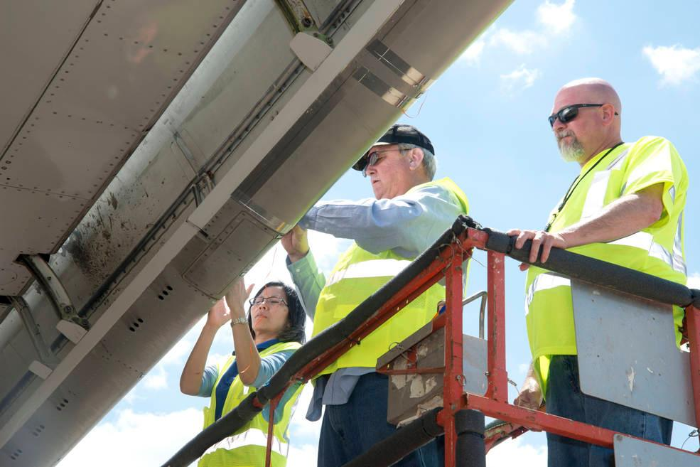 NASA and Boeing researchers counting insect residue on the right wing of Boeing's ecoDemonstrator 757 aircraft