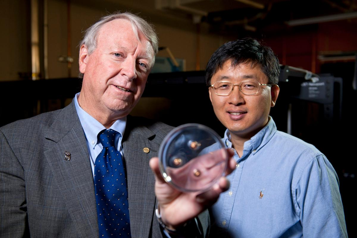 Edwin Thomas, left, and Jae-Hwang Lee holding a polymer material containing three bullets (Photo: Tommy LaVergne, Rice University)