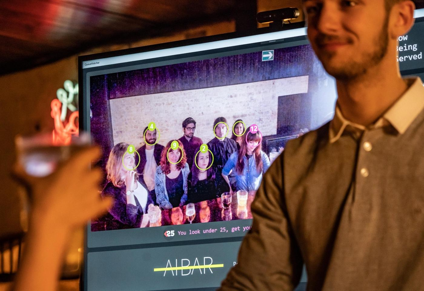 The A.I. Bar system makes use of a standard webcam that scans waiting customers and assigns each one with a virtual queue number, which can be seen on a display screen above the bar
