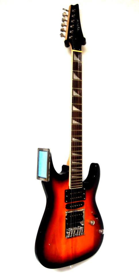 The Tepoe Guitar features a small computer screen at the upper horn of the instrument that contains video lessons, chord pattern diagrams, guitar tab, and backing tracks to help the beginner learn to play