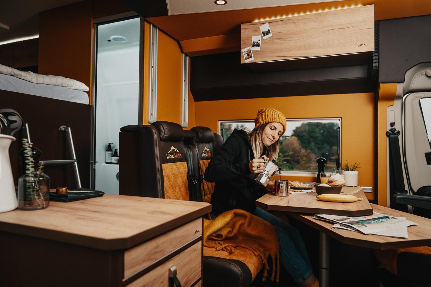 The WoodVans Moto packs in the dual-seat bench/table/swivel cab seat dinette typical of European camper vans-