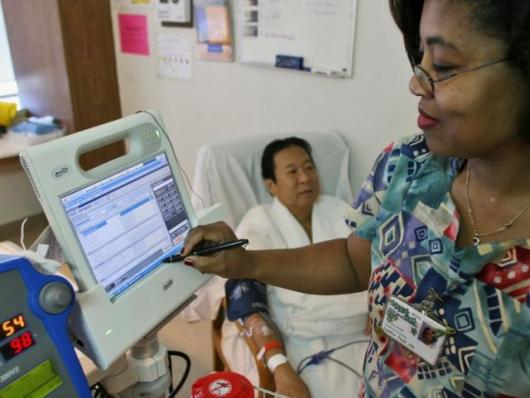 Nurse Agatha Ekeh, right, updates patient Charles Khim's medical record using Motion Computing's C5, the first product based on Intel's mobile clinical assistant platform, Tuesday, Feb. 20, 2007, at UCSF Medical Center in San Francisco.