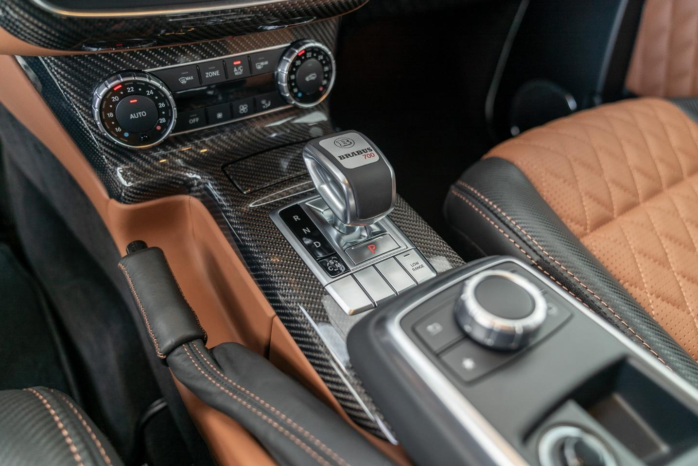 The interior is a two-tone black/brown leather job with carbon accents