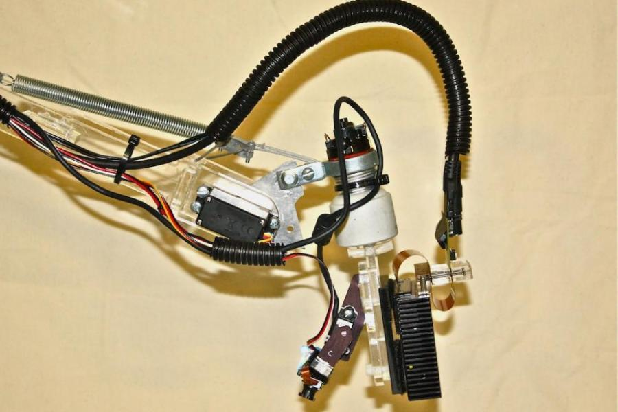 A prototype of the LuminAR Bulb with a camera and Pico-projector mounted on a robotic arm