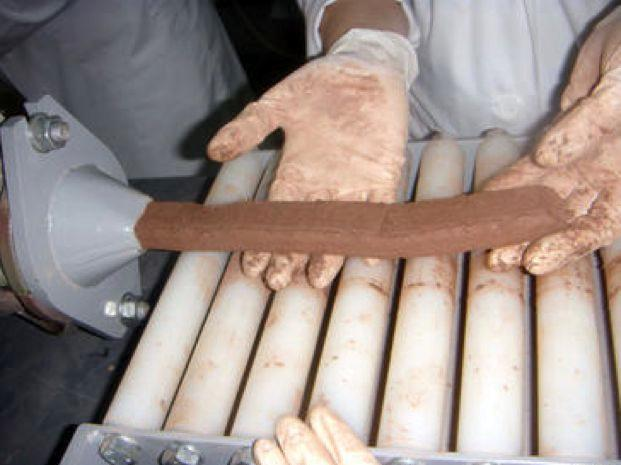 A length of the paper-based bricks being extruded