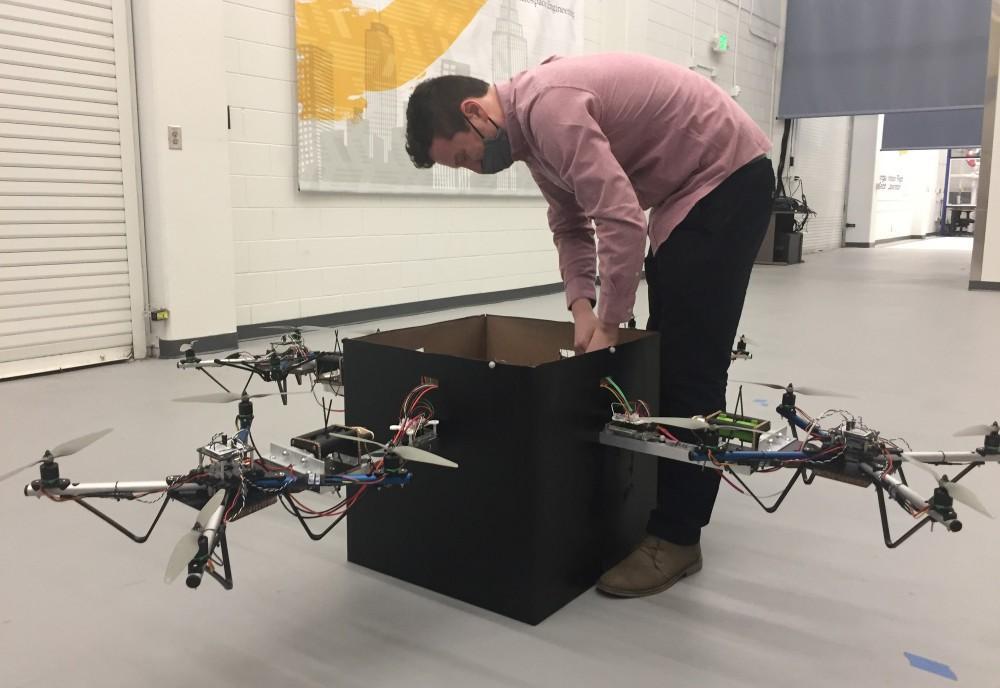 Graduate student Kevin Webb adjusts the control system