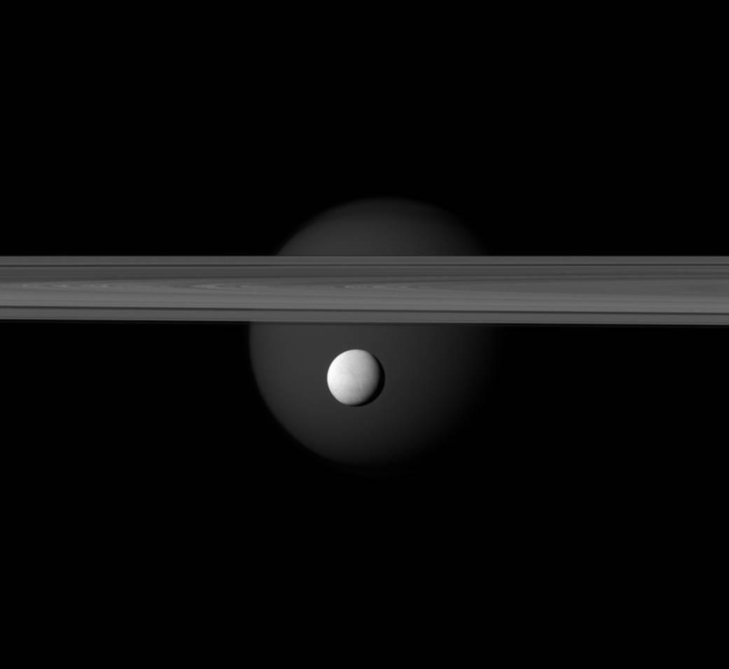 Enceladus in front of Saturn's rings, with the planet's larger moon Titan in the background