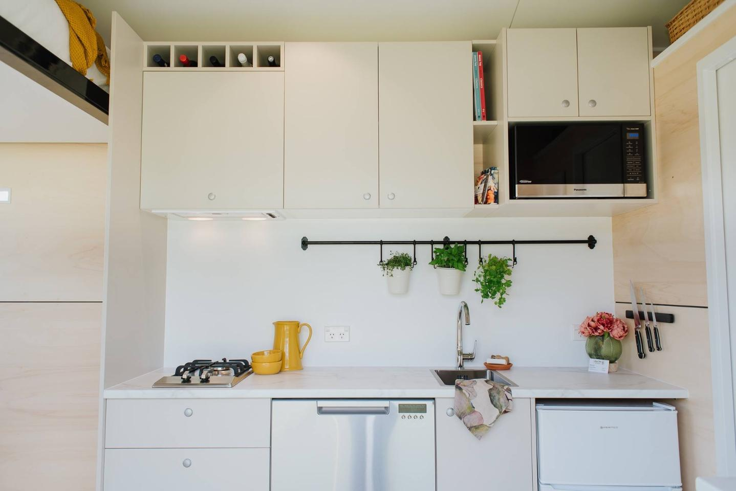 Visitors enter the Camper Tiny House into its kitchen area