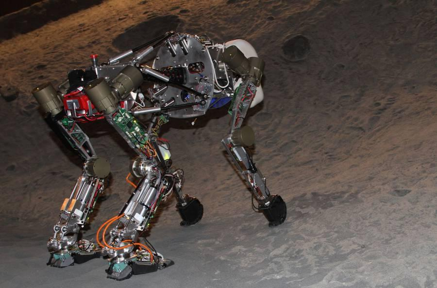 The four-legged iStruct Demonstrator robot in DFKI's artificial crater environment (Photo: Daniel Kühn, DFKI GmbH)