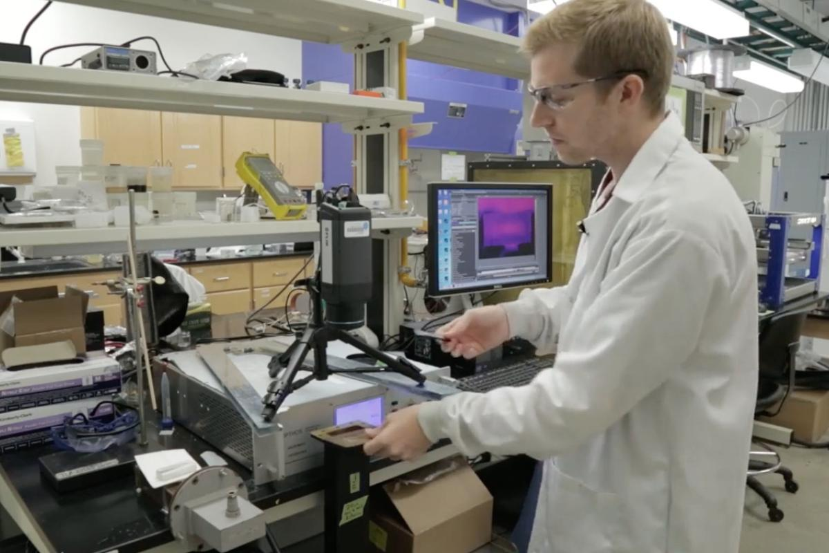 Brandon Sweeney places a 3D-printed item in the microwave source