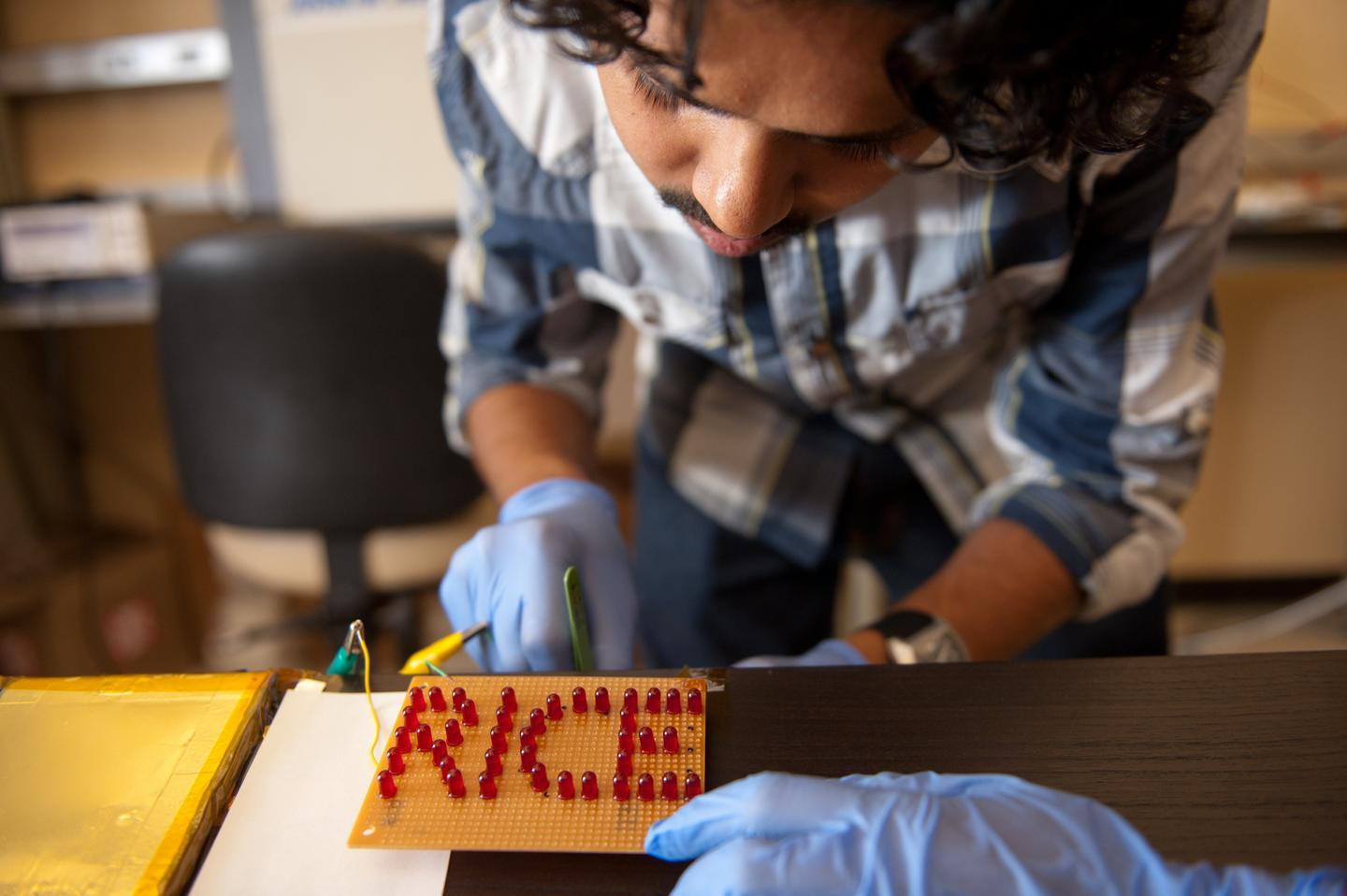 Rice University graduate student Charudatta Galande wires an array of LEDs to a set of batteries painted on the surface of ceramic tiles (Photo: Jeff Fitlow/Rice University)