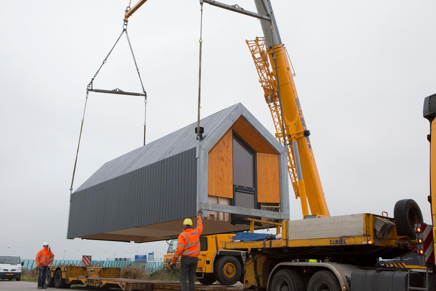 The Heijmans ONE is transported by truck and placed into position by crane