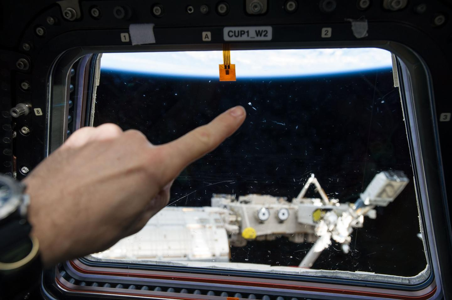 Photographic documentation of a Micro Meteor Orbital Debris strike on one of the window's within the International Space Station