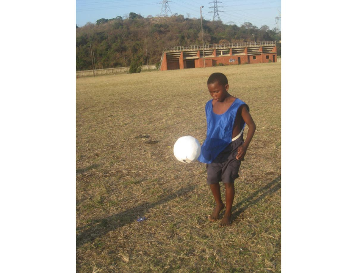 A young lad tests out the prototype sOccket power-generating soccer ball in a Durban, South Africa, trial of the device