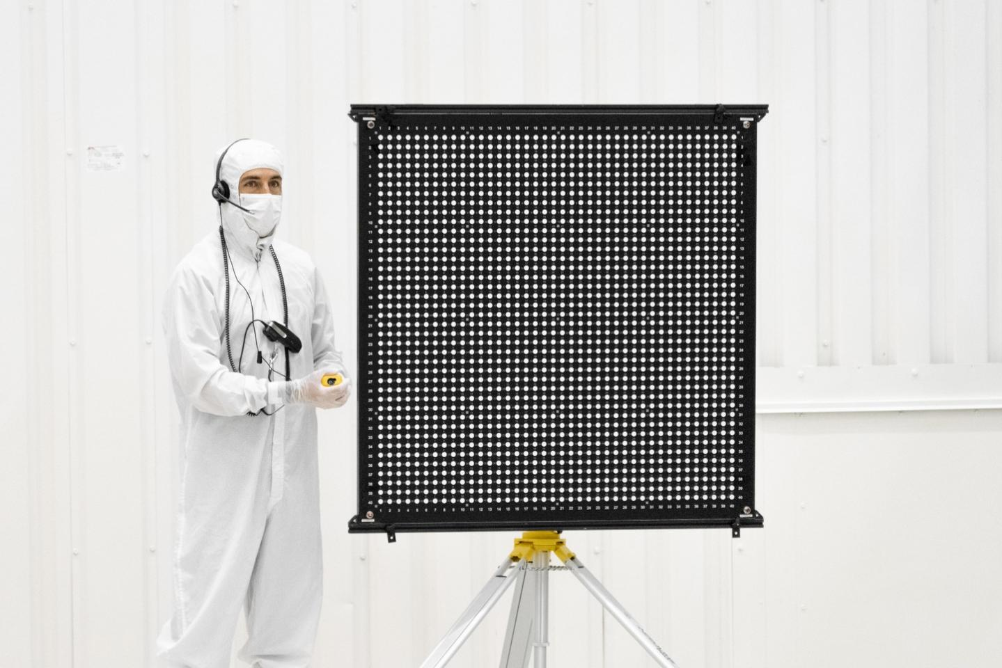 Engineer Chris Chatellier stands next to a target board with 1,600 dots