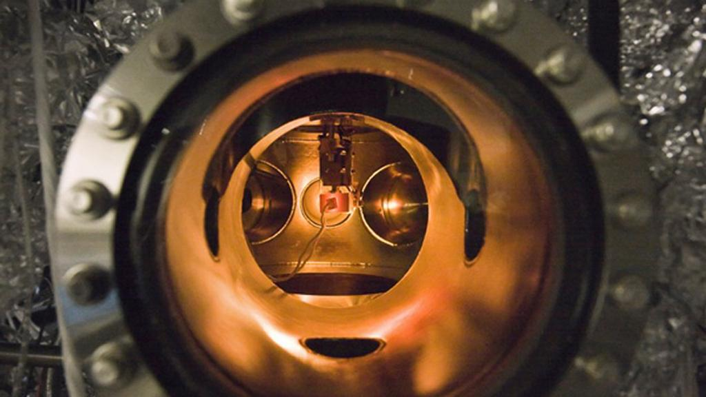 A small PETE device made with cesium-coated gallium nitride glows while being tested inside an ultra-high vacuum chamber (Image: Nick Melosh)