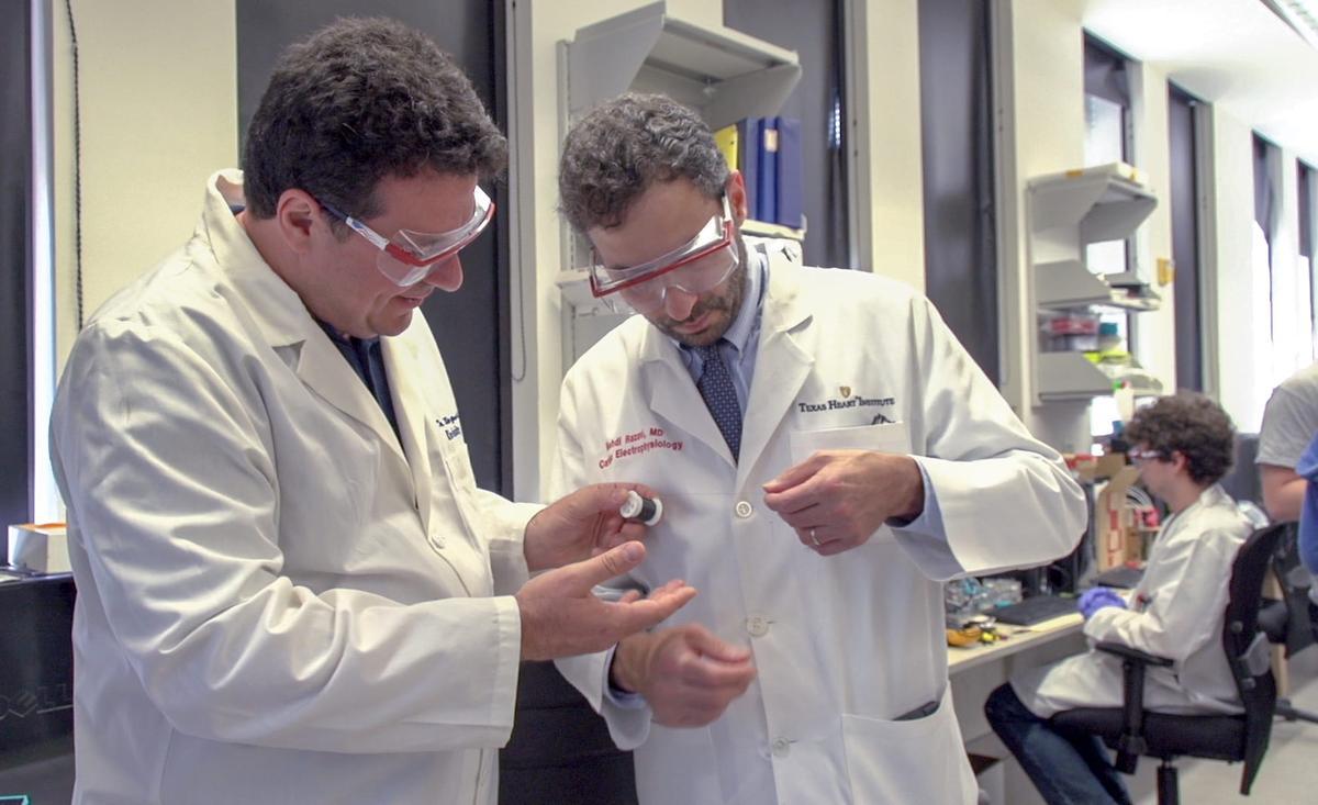 Dr. Mehdi Razavi (right) checks a thread of carbon nanotube fiber with studyco-author andRice Professor Matteo Pasquali
