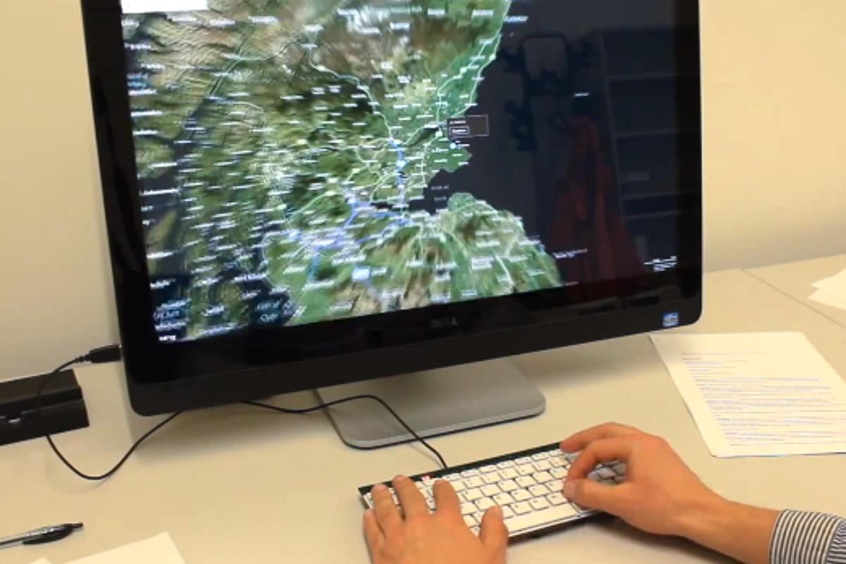A user zooms in on a map by pinching their fingers on the keyboard