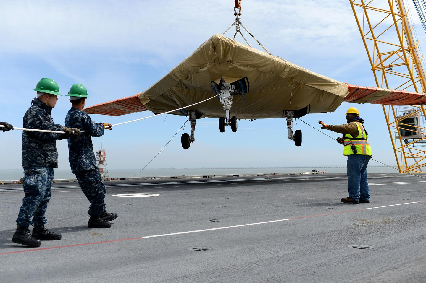 An X-47B Unmanned Combat Air System (UCAS) demonstrator is loaded onto the flight deck of the aircraft carrier USS George H.W. Bush (CVN 77) (Photo: US. Navy/Mass Communication Specialist 2nd Class Tony D. Curtis)